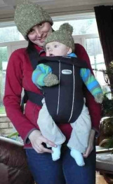 A mum carries her baby front facing out in a mass-produced carrier. They have matching bobble hats.