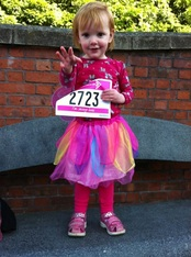 One of the Sheffield Race for Life-rs toddlers, all in pink, poses with her mum's running number