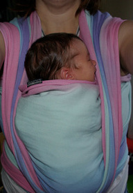 A new baby is snuggled in to his mum's front in a pink and blue woven wrap.